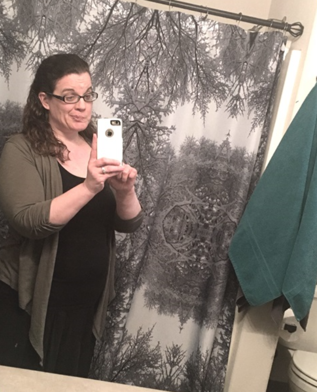 woman taking a selfie in a bathroom mirror...what not to do for a selfie...be mindful of your background